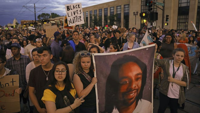 Supporters of Philando Castile hold a portrait of Castile as they march along University Avenue in St. Paul, Minn., leaving a vigil at the state capitol, Friday. The vigil was held after St. Anthony police Officer Jeronimo Yanez was cleared of all charges in the fatal shooting last year of Castile.