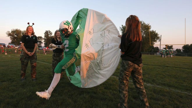Southeast Warren senior Blake Bauer explodes through a banner during player introductions. Southeast Warren hosted Oakland Riverside for Homecoming in Lacona on Sept. 23, 2016, winning 39-14.