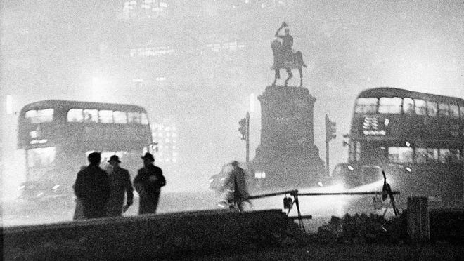 Double-decker buses circled the Prince Albert statue at Holborn Circus in London, England, in the smog on the night of Dec. 6, 1952.