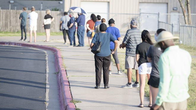 Voters stand in line for nearly 20 minutes early Tuesday at the Pflugerville Independent School District Rock Gym to vote in the July 14, 2020, primary runoff election.