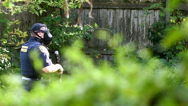 A Columbia police officer wearing a gas mask moves toward an apartment building where a fugitive was barricaded Wednesday after more than a dozen tear gas canisters were fired to force the man's surrender.