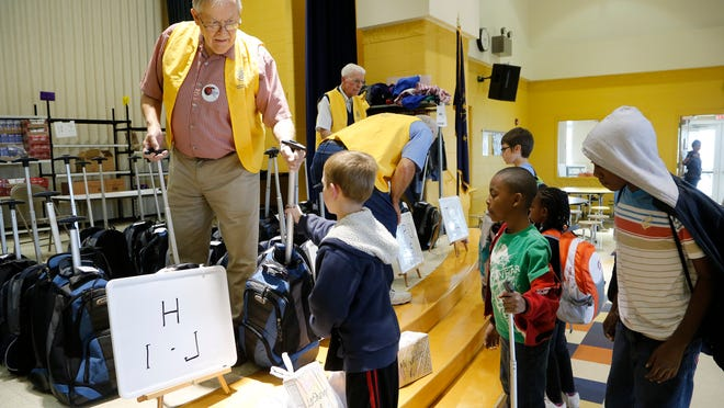 Dick Rahdert, left, and other members of Lafayette Rotary Club distribute backpacks from Food Finders Food Bank.