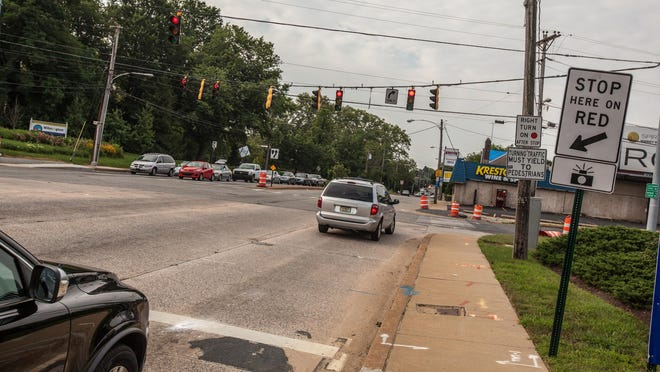 A minivan turns onto Broom Street at Concord Avenue, where a red-light camera is installed.