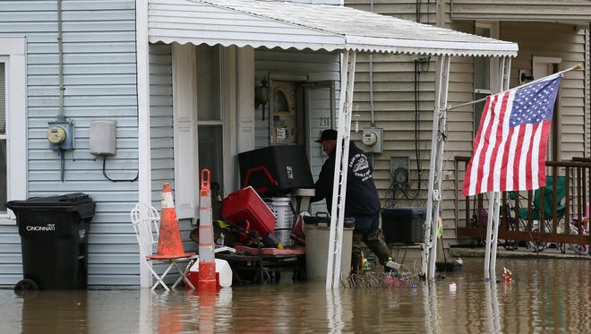 Fred White, enters his Setchell Street home in the East End, Sunday, Feb. 25, 2018, in Cincinnati. The Ohio River is expected to crest at 60.7 feet by Sunday evening, according to the National Weather Service. The river rose above the 60 feet mark for the first time in two decades Sunday morning.