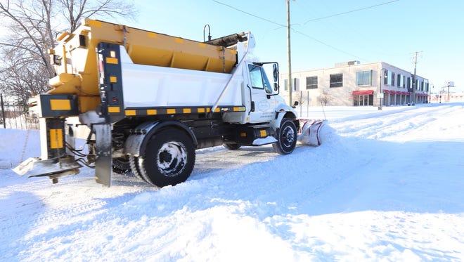 A snow plow makes its way down Bagley Street in the Hubbard Richard neighborhood in southwest Detroit Feb. 2, 2015.