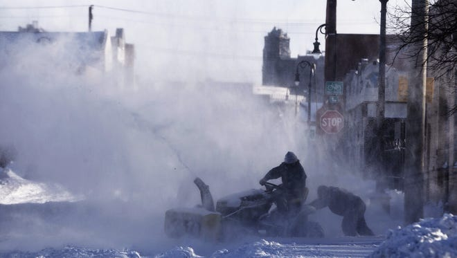 A snowblower needs a little push while cleaning up on Bagley Street in Southwest Detroit on Monday, February 2, 2015.