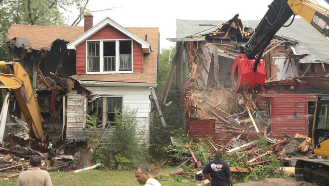 Demolition crews tear down abandoned houses on Turner Street in Detroit in August 2013 following a press conference to kick off the state's largest residential blight removal effort. Five abandoned houses were demolished on the same block.