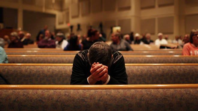 A community member prays before the start of the Kalamazoo Community Prayer Service at Centerpoint Church, Sun. Feb 21, 2016.