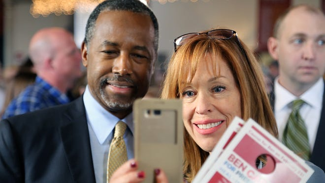 Republican Ben Carson takes a selfie with a supporter during an appearance at Piper's Opera House in Virginia City on Feb. 22, 2016.