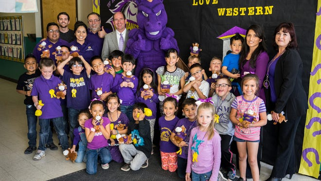 First-grade students at Harrison Schmitt Elementary School, along with WNMU officials and classroom teachers Denise Ruelaz and Sonia Castillo, at far right, gather after being presented letters of acceptance from the university on Friday.