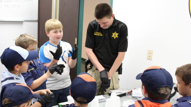 The Scouts put on gloves while investigator Tim Stavely teaches them about fingerprinting.
