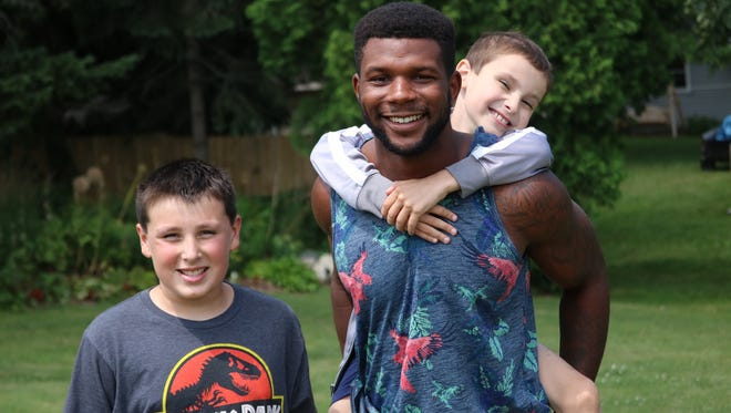 From left: Jon Deppiesse, Michael Esiobu and Mason Deppiesse pose in the backyard of Jon and Mason's Cedar Grove home on July 13, 2016. Following Mason's cancer diagnosis last year, Esiobu befriended the brothers, providing support and fun through the ups and downs of Mason's journey since then.