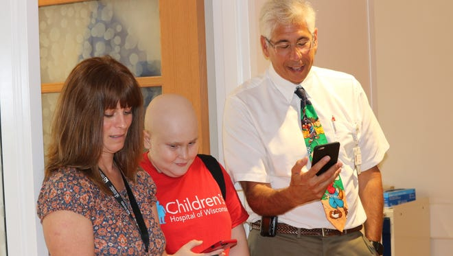 From left: Dawn Wood, Kyle Wood and Dr. David Margolis have latched onto the Pokemon Go craze, which has helped Kyle, who recently had a bone marrow transplant, get exercise and build up his strength at Children's Hospital in Milwaukee.