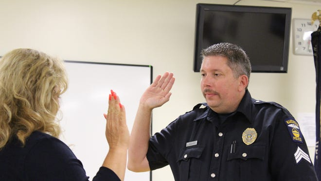 Safety-service director Lori Cope swears in Chad Brubaker as the Mansfield Police Department's newest lieutenant on Tuesday.