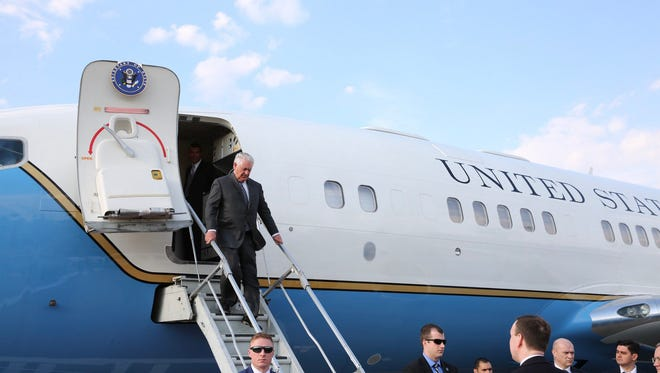 Secretary of State Rex Tillerson (top) is pictured disembarking his plane as he arrives at the Vnukovo airport, in Moscow, Russia,