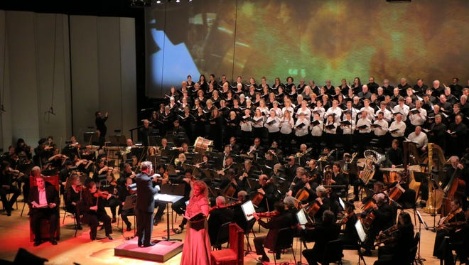 """Soloists Michelle DeYoung and Anthony Dean Griffey in the foreground, while projections played across a large screen behind the May Festival Chorus and Cincinnati Symphony, led by Michael Francis in the May Festival's """"Dream of Gerontius."""""""
