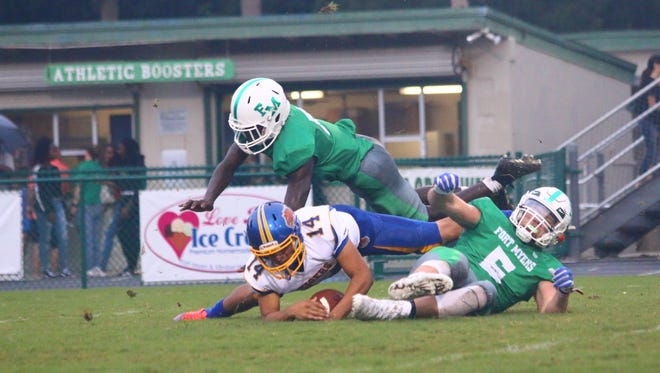 Fort Myers High's Jordan Weatherbee, right, tackles Clewiston punter Jose Benitez after he fumbled the snap on a fourth down on Saturday, Aug. 26, 2017.