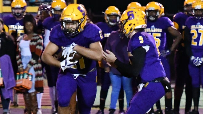 Smyrna quarterback Alex Bannister hands off to junior tailback Blake Watkins during a recent game. The Bulldogs will play host to Independence in the first round of the 6A playoffs Friday.