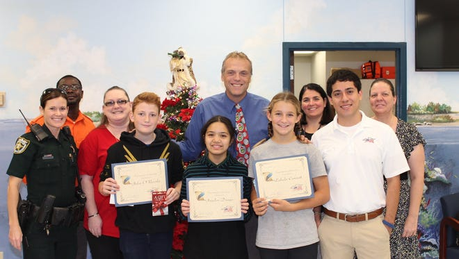From left are Deputy Christine Smith, Paris Lee, Christine Persick, Principal Glenn Rustay, Assistant Principal Meghan Drost, Kathleen Egan and Adrian Garcia from Step Up America congratulate the winning students, from left in front, John O'Rourke, Jayden Diago and Lahela Cornett.