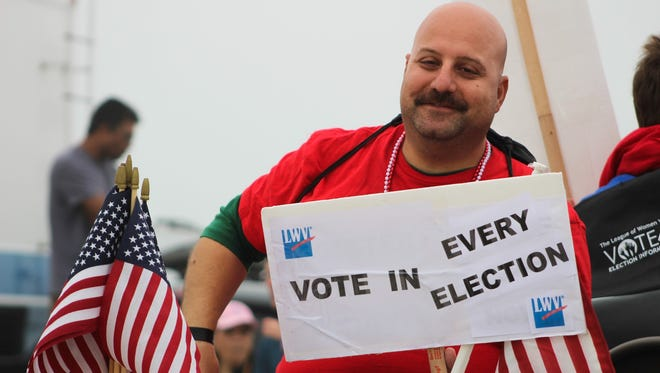 A man holds up a League of Women Voters sign encouraging voting.