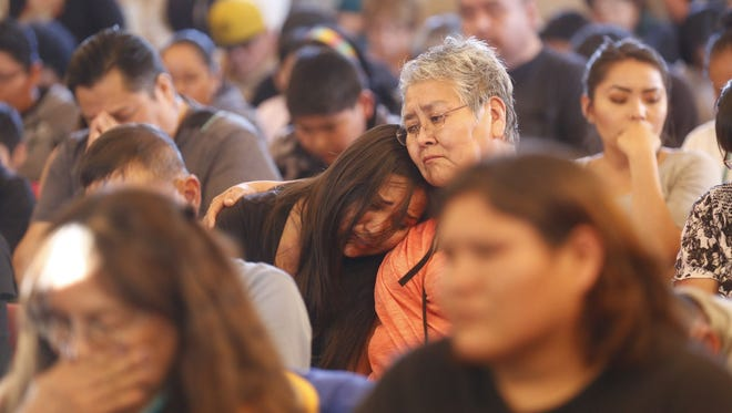 Community members comfort one another May 2, 2016, at a vigil for Ashlynne Mike at the San Juan Chapter house in Lower Fruitland.