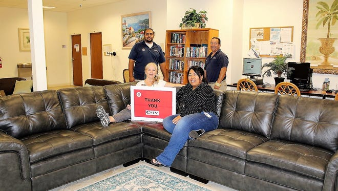 Women's Auxiliary member Lori Baird sits with Compassion House Shelter Coordinator Kim Tolbert on the new sofa donated to the shelter by City Furniture. Standing are City Furniture employees Michel Cruz and Lance Phillips.