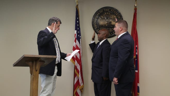 Chief Bond Tubbs swears in two new agents of the Alcoholic Beverage Commission.
