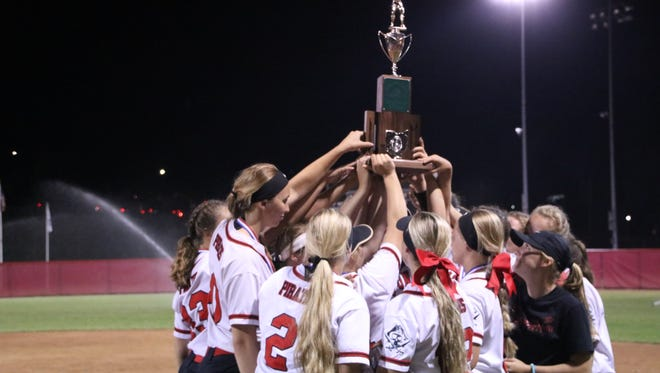 Cardington's softball team hoists the Division III state runner-up trophy after suffering a 9-4 loss to Warren Champion Saturday night in Akron.