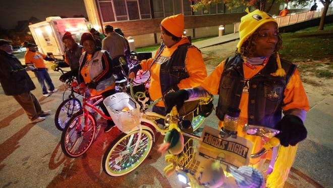 GLOW Detroit member Velma Massey (right) of Pontiac Hood 2 and Hood Riderz member Jacqueline Goodlett (center) of Detroit prepare to patrol neighborhoods with other bike club members from GMOB Detroit and GLOW Detroit bike groups while volunteering for Angels' Night patrol at Northwest Activities Center in Detroit on Thursday October 30,2014.