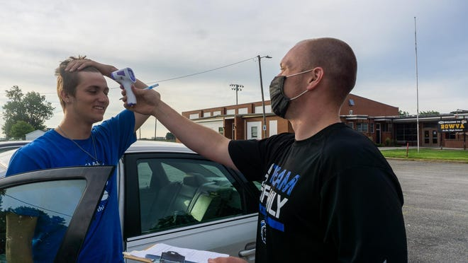 Joshua Dunn, left, gets his temperature taken by Mid-County football coach Grant Gullstrand before Friday's workouts at ROWVA High School in Oneida.
