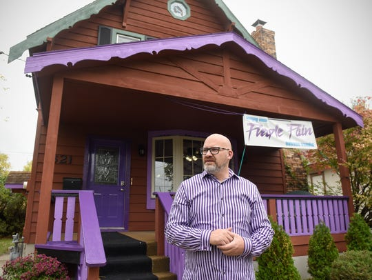 Erik Cagle stands outside his new tattoo studio, Purple