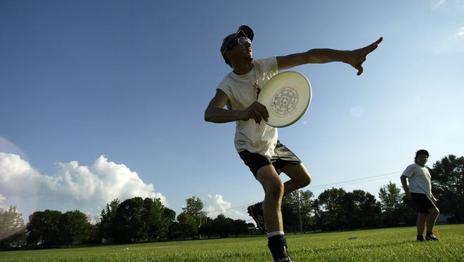 Eric Norris pulls (or throws off) to the dark team during Tuesday evening's Ultimate Frisbee masters team practice in Forest Park.  Norris and several other teammates from the LP's practice every Tuesday night and frequently compete nationally.