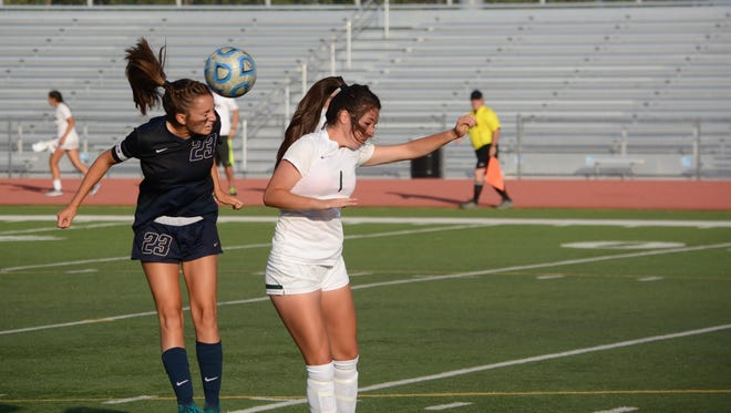 Piedra Vista's Reagan Cordell passes the ball with her head back to the center of the pitch against Farmington's Mikayla Aragon Thursday at Hutchison Stadium.