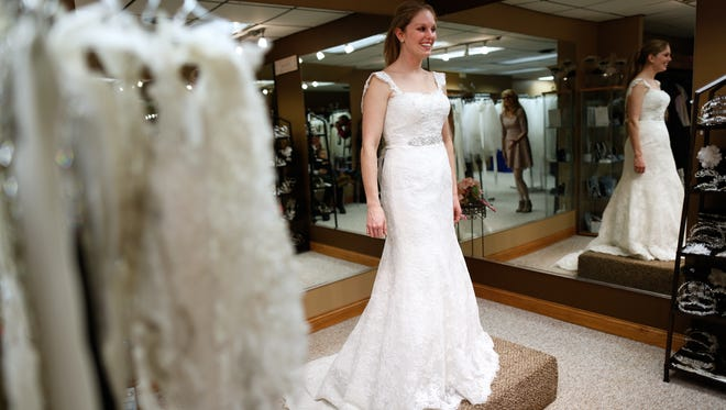 Kasey Bink, 25, looks to her mother and sister for opinions on one of the dresses she tried on at Tie the Knot Bridal Boutique in Green Bay.