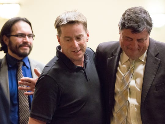 Ross Flynn, center, embraces his attorney Jeff Lahann,