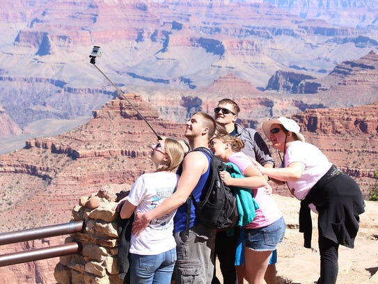 Tourists pose for a selfie at Grand Canyon National