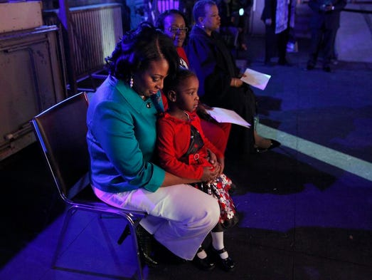 Mayor Lovely Warren, left, holds her daughter Taylor Granison, right, as she listens in the wings of the stage at the  Auditorium Theatre during her public inaugural ceremony.