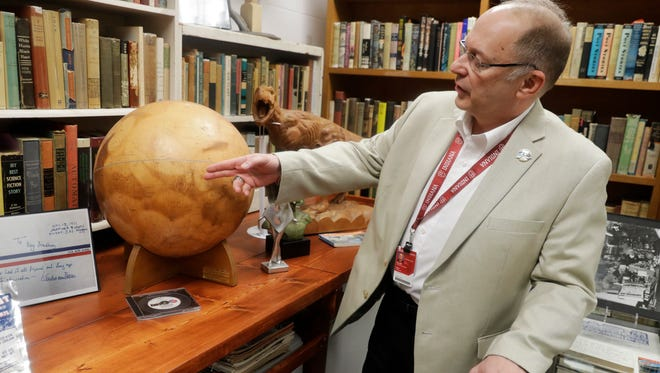 In this Thursday, April 12, 2018, photo, Center for Ray Bradbury Studies director Jonathan Eller points out the location of Gale Crater on the Mars globe, in Indianapolis. The globe presented to Ray Bradbury for his support of NASA's Mariner 9 Mars orbital mission in 1971.