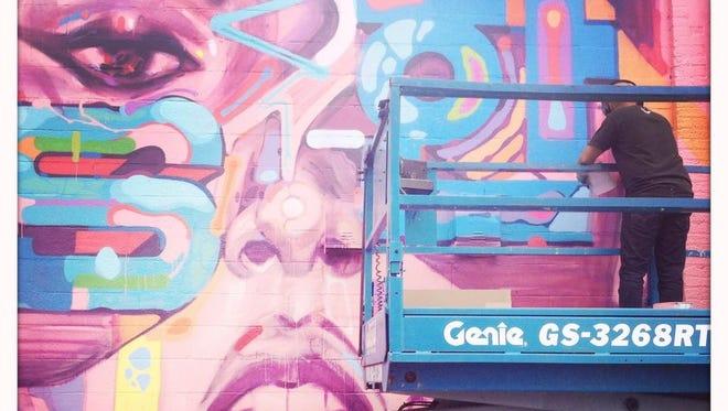 Sam Rodriguez paints his mural on Greenleaf Street on Saturday.