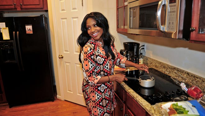 Kimberly Rodriquez prepares dinner for her children at their home, which she rents out on Airbnb for $300 to $400 a night.