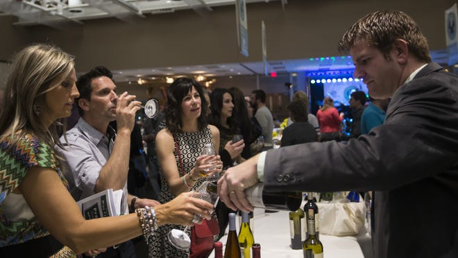 Server Mark Goldsberry pours samples of Fetzer brand wine during the WineFeast benefit in 2014 at the Oshkosh Convention Center. This year's event is Saturday, April 29.