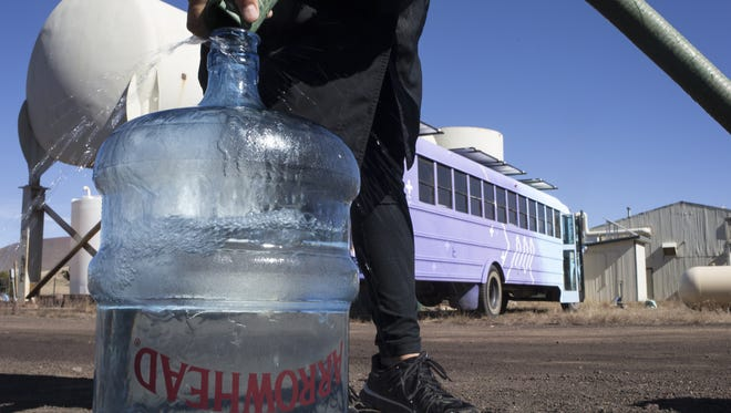 A bottle is filled with well water that will be purified in a desalination bus built for Navajo Nation residents.