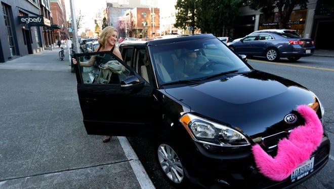 In this file photo, Katie Baranyuk gets out of a car driven by Dara Jenkins, a driver for the ride-sharing service Lyft, after getting a ride to downtown Seattle. General Motors now owns a 9% stake in Lyft. Toyota, Volkswagen and BMW also made recent investments in ride-sharing platforms.