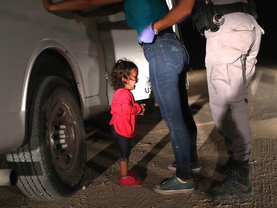 A 2-year-old Honduran asylum seeker cries as her mother
