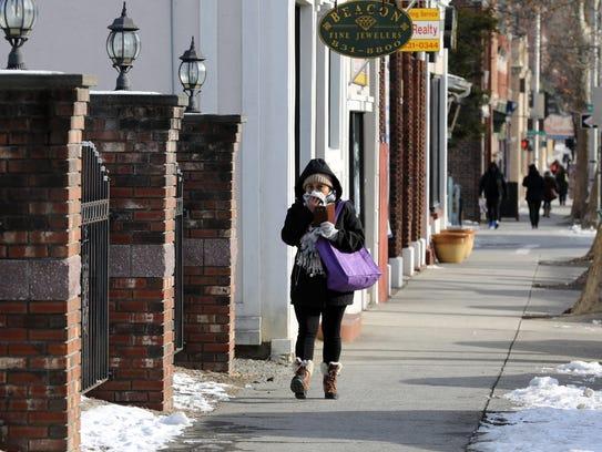 Bundled up pedestrians walk along Main Street in Beacon,