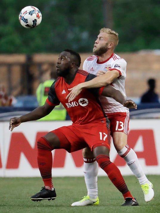 Toronto FC forward Jozy Altidore, left, tries to control the ball as New York Red Bulls forward Mike Grella (13) defends during the first half of an MLS soccer match, Friday, May 19, 2017, in Harrison, N.J. (AP Photo/Julio Cortez)