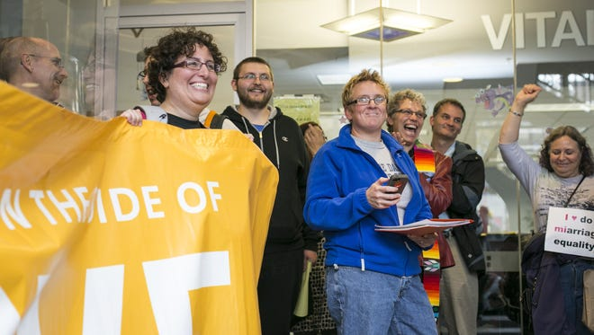 Couples and gay marriage supporters gather at the Washtenaw County Court Building in Ann Arbor, Mich.,  on Oct. 16, 2013.