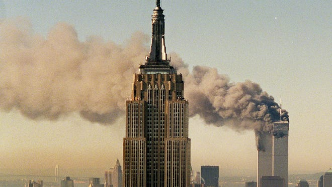 The twin towers of the World Trade Center burn behind the Empire State Building in New York on Sept. 11, 2001.