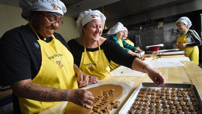Sonya McCraney, left, and Cynthia Sieling, center, members in the St. Francis Homeless Project, have fun making dog biscuits at Institute of Technology, employed in the  Dogs Dig Em' ministry. The St. Francis Homeless Project employs former homeless women who complete drug/alcohol rehab. After the six-month program is up, the ministry helps them find other work.