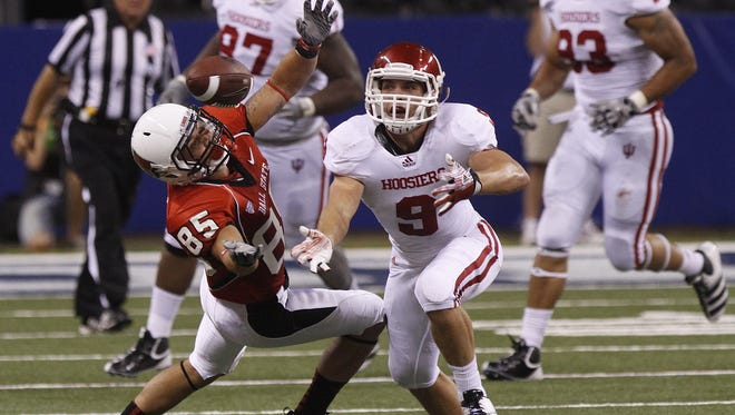Ball State's Jack Tomlinson and Indiana's Greg Heban dive for a loose ball during their game at Lucas Oil Stadium in Indianapolis on Saturday, Sept. 3, 2011.